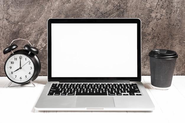 Despertador e copo de café descartável com um laptop aberto na mesa branca Foto gratuita