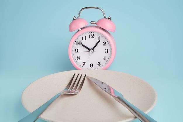 Despertador e prato com talheres. conceito de jejum intermitente, hora do almoço, dieta e perda de peso Foto Premium
