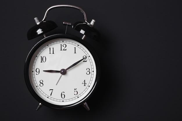 Despertador em fundo preto Foto Premium