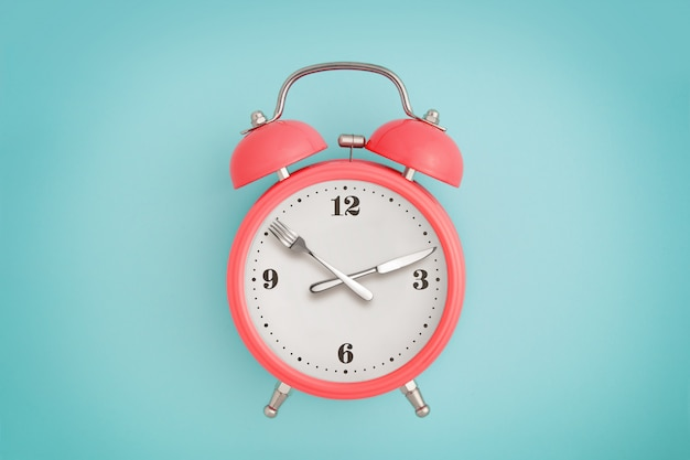 Despertador. garfo e faca em vez de ponteiros do relógio. conceito de jejum intermitente, hora do almoço, dieta e perda de peso Foto Premium
