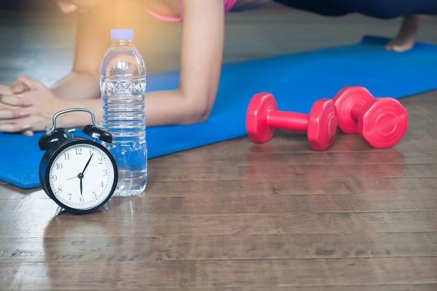 Despertador, garrafa de água, halteres e mulher asiática yoga em casa no fundo, conceito de exercício e estilo de vida, foco seletivo Foto Premium