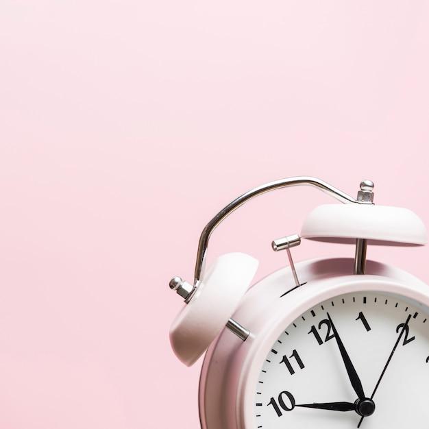 Despertador mostrando o tempo 10'o relógio contra fundo rosa Foto gratuita