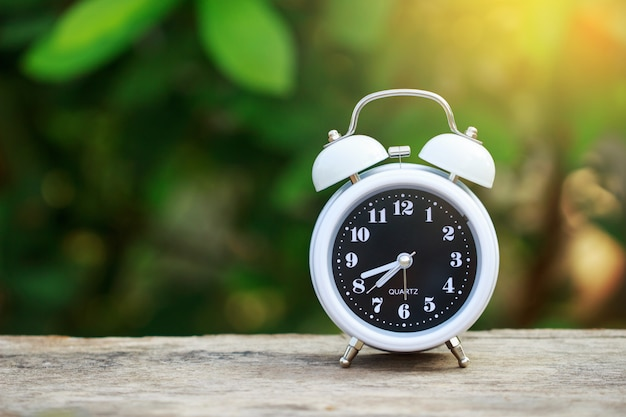 Despertador na mesa com borrão verde folhas fundo e sunray Foto Premium