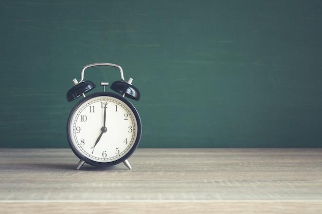 Despertador na mesa de madeira no fundo do quadro-negro em sala de aula Foto Premium