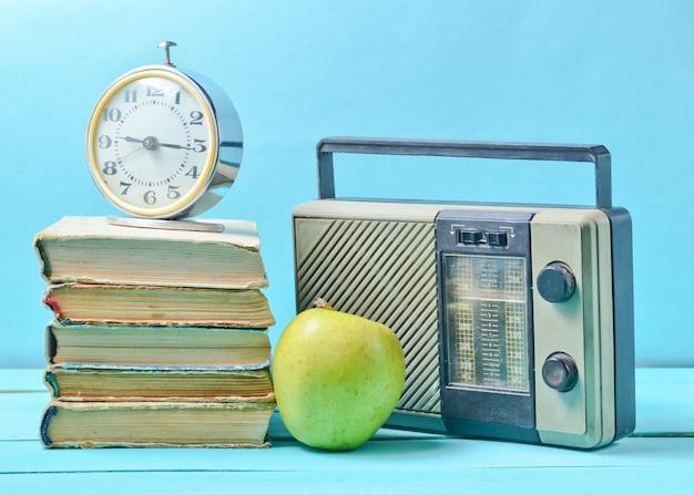 Despertador na pilha de livros antigos, receptor de rádio, maçã em um azul. Foto Premium
