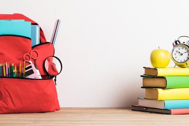 Despertador na pilha de livros e mochila escolar bem embalada com suprimentos Foto gratuita