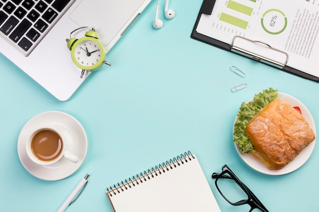 Despertador no laptop, fones de ouvido, o bloco de notas em espiral, óculos e plano de orçamento em pano de fundo azul Foto gratuita