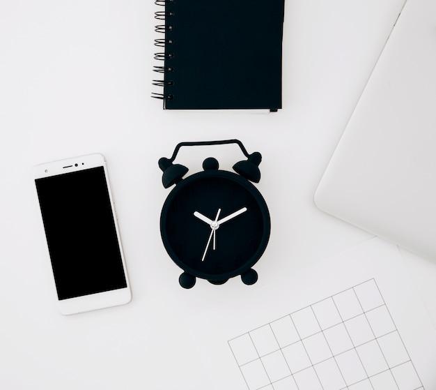 Despertador preto; bloco de notas em espiral; smartphone; página e laptop na mesa branca Foto gratuita