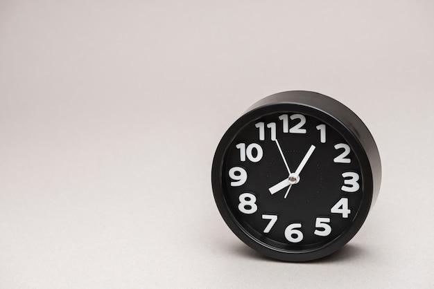 Despertador preto redondo contra um fundo cinza Foto gratuita