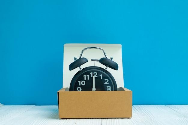 Despertador retro na caixa ou na bandeja marrom de cartão da entrega na madeira branca e no fundo azul da parede, no tempo e no conceito do fim do prazo. Foto Premium