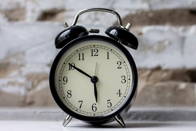 Despertador retrô na mesa no fundo da parede de tijolo Foto Premium