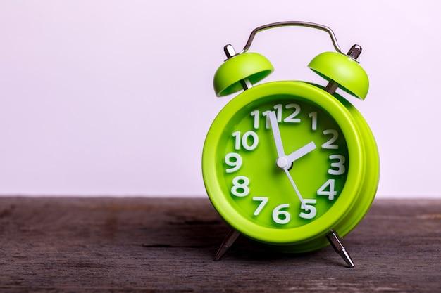 Despertador retro verde vintage na mesa de madeira, com espaço vazio para o seu texto. clássico com campainha dupla. Foto Premium