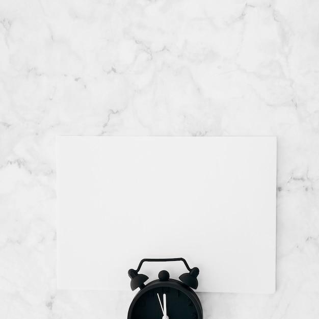 Despertador sobre o papel em branco branco contra o plano de fundo texturizado mármore Foto gratuita