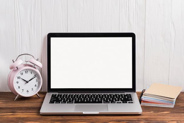 Despertador; um laptop aberto e notebook empilhados na mesa de madeira contra a parede Foto gratuita