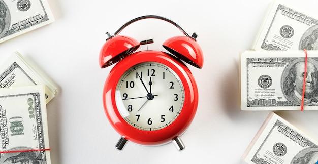 Despertador vermelho brilhante em estilo retro, sobre uma pilha de dólares e euros de papel. tempo é dinheiro. conceito de negócios. Foto Premium