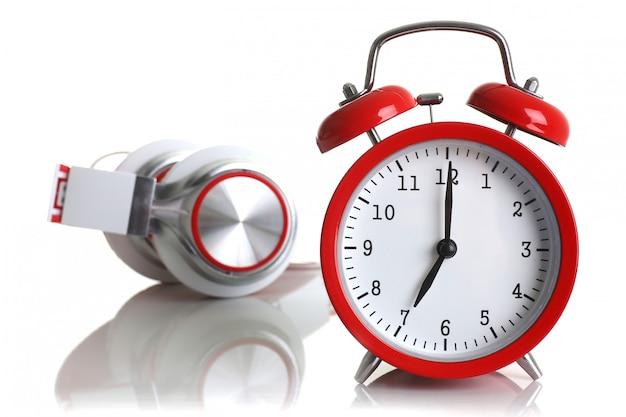 Despertador vermelho com fones de ouvido isolado no fundo branco mostra sete minutos da manhã, é hora de acordar e tomar café da manhã ou correr à noite para ir trabalhar ouvir música .. Foto Premium