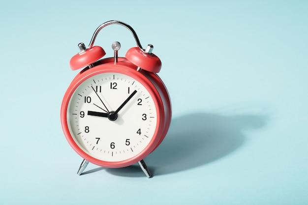 Despertador vermelho com sombra. nove e nove em ponto Foto Premium
