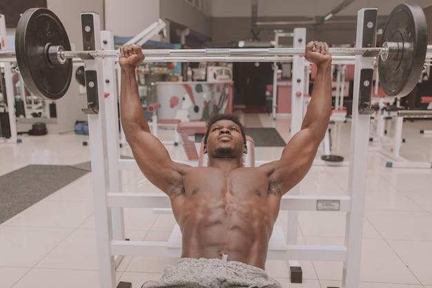 Desportista africana exercitando na academia Foto Premium