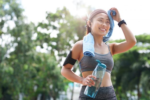 Desportista alegre com garrafa e toalha Foto gratuita