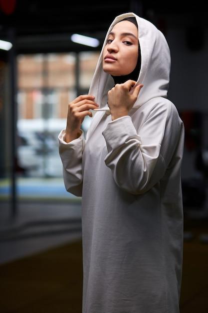 Desportista árabe está posando no ginásio após o treino, retrato de uma senhora muçulmana em hijab branco posando, olhando para a câmera. Foto Premium