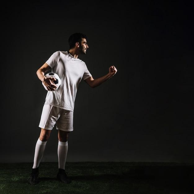 Desportista atraente com bola comemorando a vitória Foto gratuita