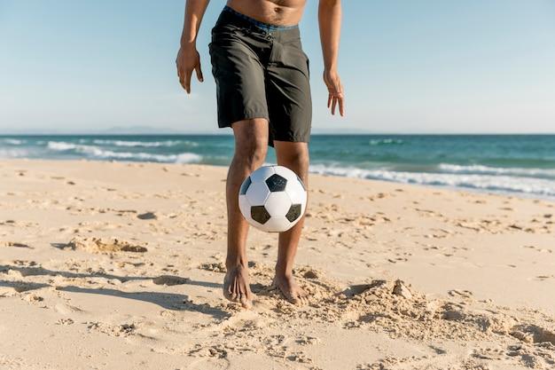 Desportista, batendo a bola na costa Foto gratuita