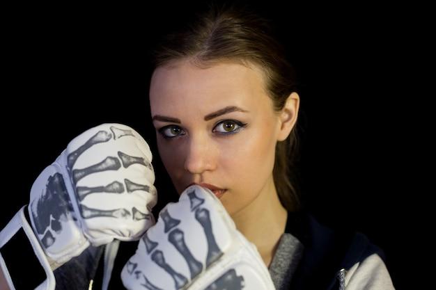 Desportista da menina nas luvas para encaixotar em um fundo preto. Foto Premium