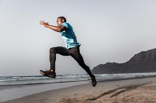 Desportista determinado a saltar perto do mar Foto Premium