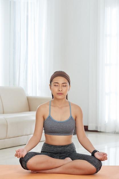Desportista étnica, meditando em casa Foto gratuita