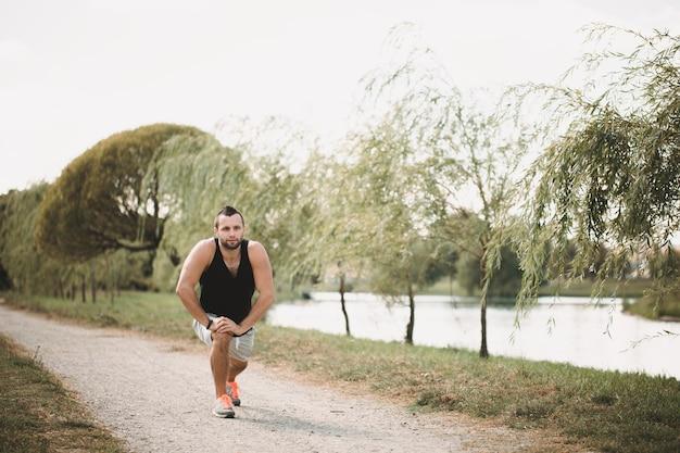 Desportista faz exercícios na rua. atleta cansado em roupas esportivas faz uma pausa. Foto Premium