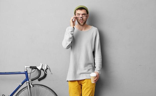 Desportista inteligente, olhando através de grandes óculos com expressão séria, tomando um delicioso café quente, indo a competições ou no ginásio. Foto gratuita