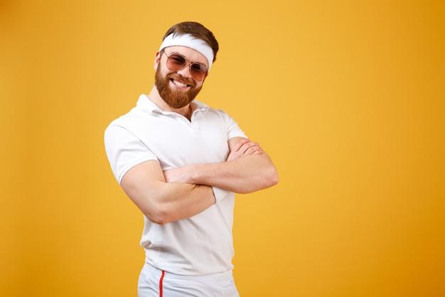 Desportista sorridente em óculos de sol com braços cruzados Foto gratuita