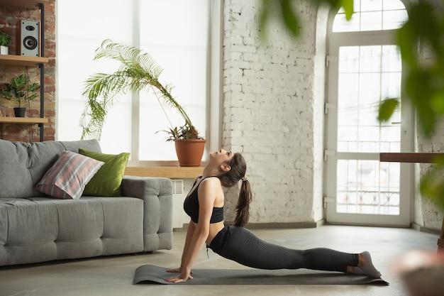 Desportiva jovem tendo aulas de ioga on-line e práticas em casa Foto gratuita