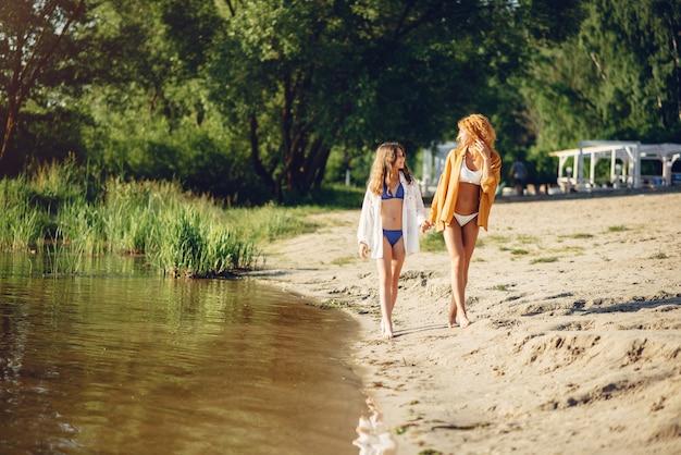 Desportiva, mãe, com, cute, filha, andar, perto, lago Foto gratuita