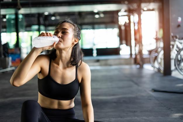 Desportiva mulher bonita exercitar relaxar e beber água com equipamento de treino Foto Premium