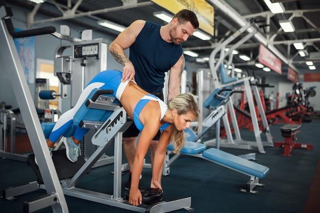 Desportiva mulher fazendo exercícios de peso com a ajuda de seu personal trainer na academia Foto Premium