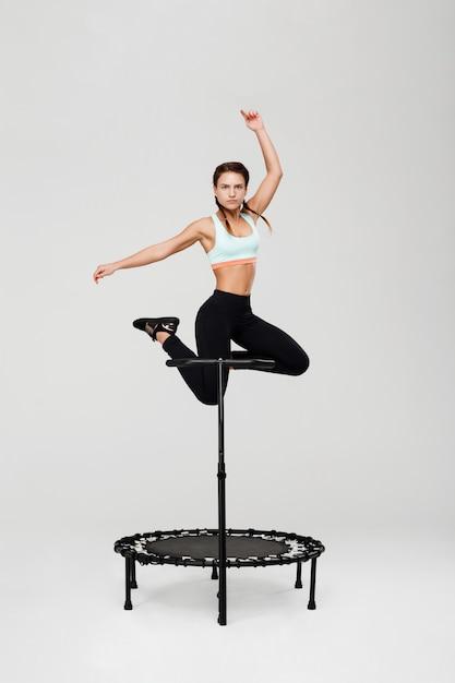 Desportiva mulher pulando com as mãos para cima rebounder com alça Foto gratuita