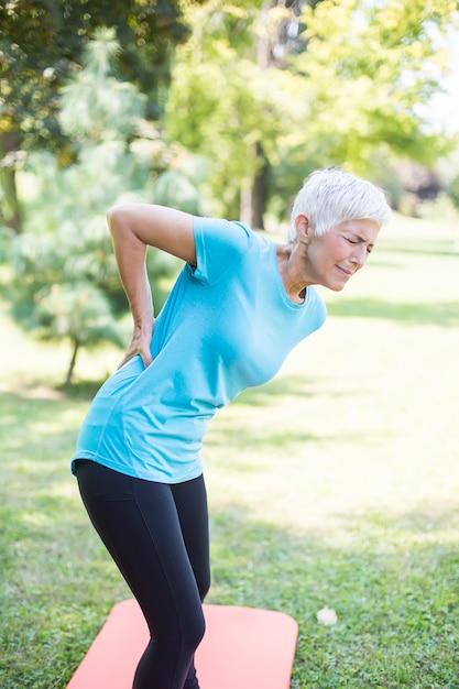 Desportiva mulher sênior tendo uma dor nas costas Foto Premium