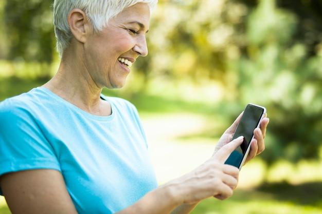 Desportiva mulher sênior usando telefone celular no parque Foto Premium