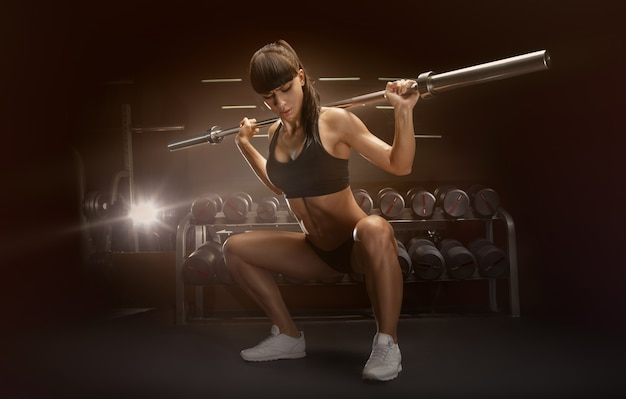 Desportiva mulher sexy fazendo agachamento no ginásio Foto Premium