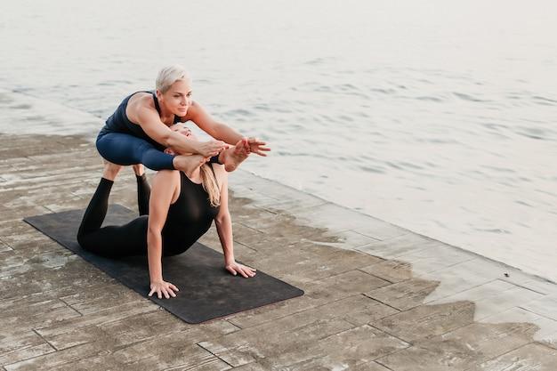 Desportivas mulheres fazendo acro yoga exercícios perto do mar na praia Foto Premium