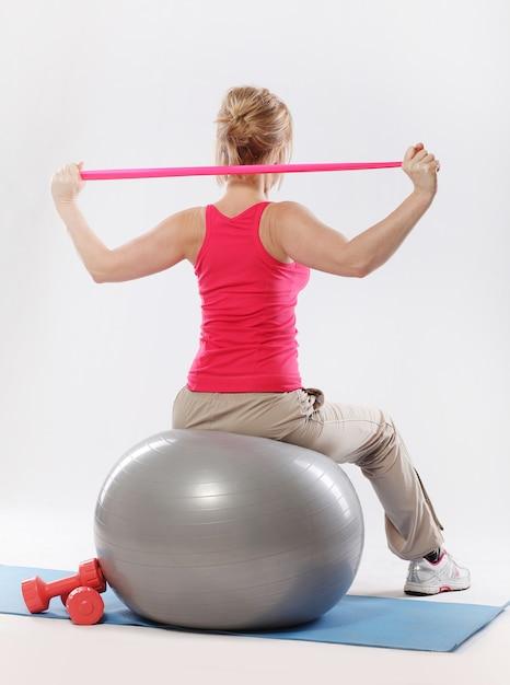 Desportivas mulheres fazendo exercícios de alongamento com bola de estabilidade de fitness Foto gratuita