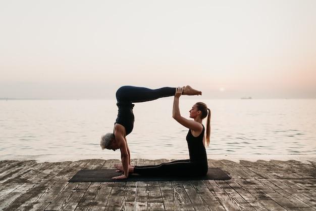 Desportivas mulheres fazendo yoga asana com pino no nascer do sol perto do mar Foto Premium