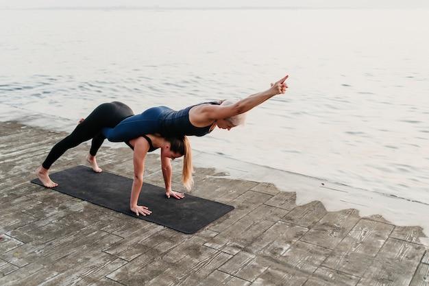 Desportivas mulheres posando em acro yoga asana ao ar livre perto do mar Foto Premium