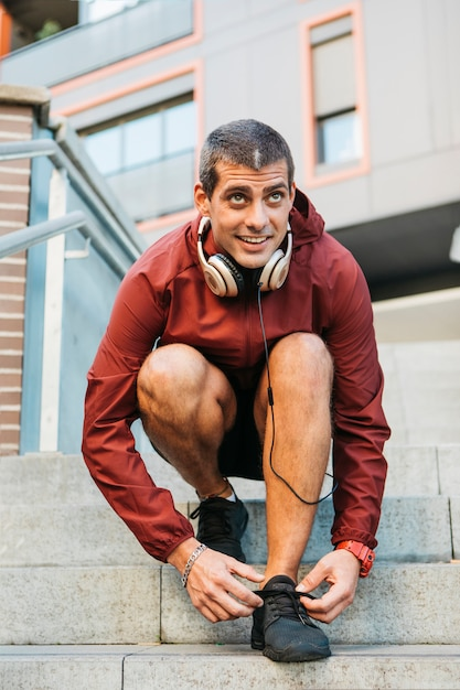 Desportivo homem amarrar sapatos em ambiente urbano Foto gratuita