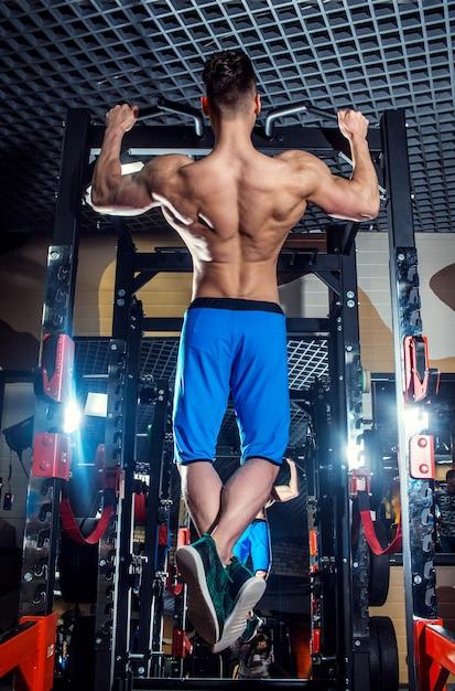 Desportivo homem com grandes músculos e uma ampla volta treina no ginásio, fitness e imprensa abdominal bombeado. Foto Premium