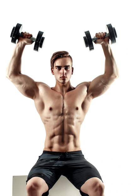 Desportivo homem em formação, bombeando os músculos das costas e mãos com halteres. Foto Premium