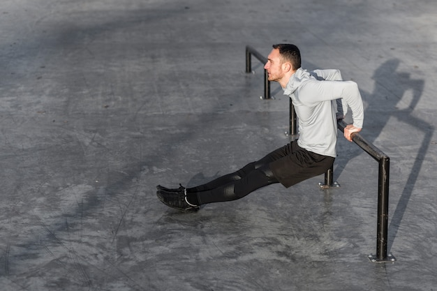 Desportivo homem fazendo exercícios de tríceps fora Foto gratuita