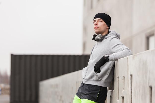 Desportivo, homem, inclinar-se, contra, parede Foto gratuita