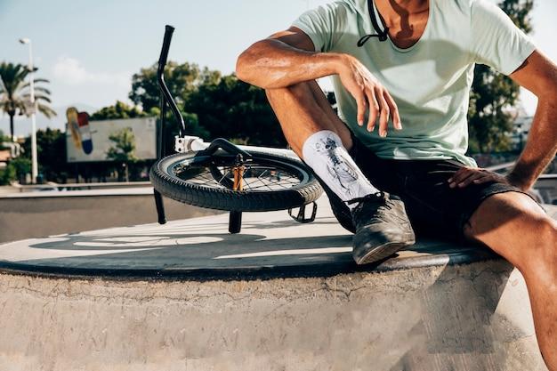 Desportivo homem parado perto de uma bicicleta de bmx Foto gratuita